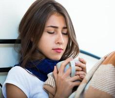 sjuk tonårsflicka med varmt te och medicin inomhus foto