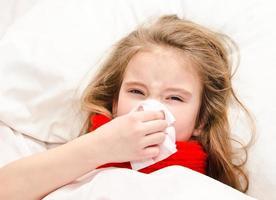 liten flicka som ligger i sängen och blåser näsan foto