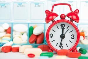 medicin i veckopill-lådan och röd väckarklocka foto