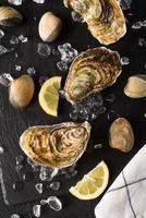 färska ostron och musslor på en svart stenplatta foto