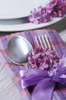 bordsinställning i violetta färger, lila blommor för dekoration. foto