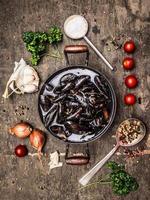 rå musslor i panna med vatten på mörk träbakgrund foto