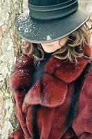 ung kvinna i päls och snöig hatt foto