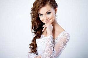 porträtt av lycklig brud i bröllopsklänning, tittar på foto