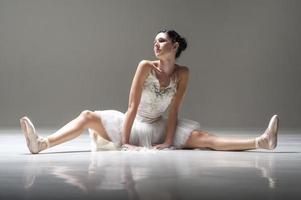 unga vackra ballerina sträckningsben på studiogolvet