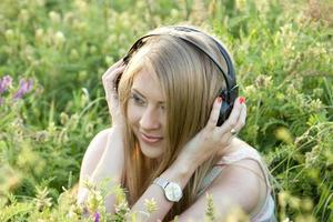 flicka med hörlurar på gräset foto