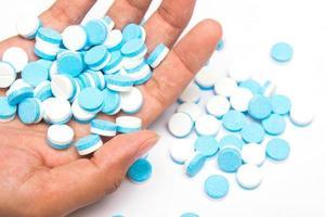 vita och blå tabletter piller till hands foto