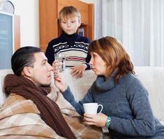 ohälsosam man omgiven av omtänksam fru och son foto