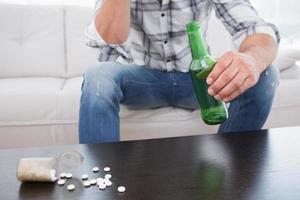 man med en öl och hans medicin lagt foto