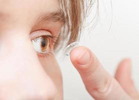 ung kvinna sätter in korrigerande lins i ögat foto