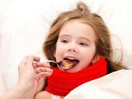 liten flicka i sängen som tar medicin med skeden foto