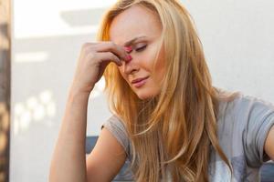 blond hår flicka sitter och lider på grund av huvudvärk. foto