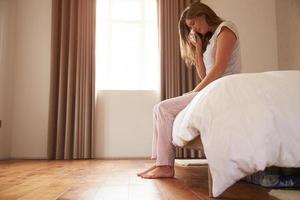 kvinna som lider av depression sitter på sängen och gråter foto