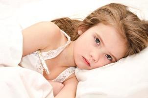 sjuk liten flicka som ligger i sängen foto
