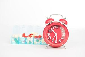 röd väckarklocka och medicin i veckopiller foto
