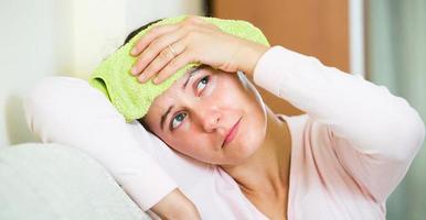 kvinna med huvudvärk hemma foto