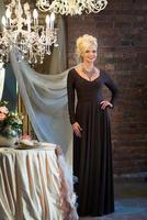 kvinna i mörk lång klänning i lyxig interiör. halsband. blond foto