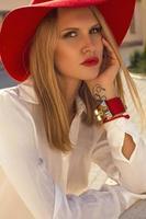 vacker flicka med blont hår i elegant röd hatt