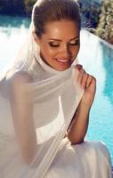 vacker leende brud med blont hår i elegant bröllopsklänning foto