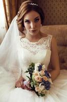 brud i lyxiga spetsar bröllopsklänning med bukett blommor foto