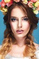 vacker ung flicka med en blommig prydnad i håret foto