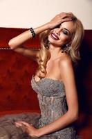 underbar kvinna med blont hår som bär lyxig paljettklänning foto
