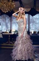 underbar kvinna i elegant klänning poserar i lyxig interiör foto
