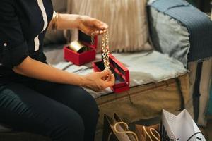närbild på ung kvinna med shoppingväskor som packar upp smycken foto