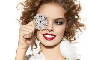 vacker flicka med kvällsmakeup leende ta cristal snöflinga foto