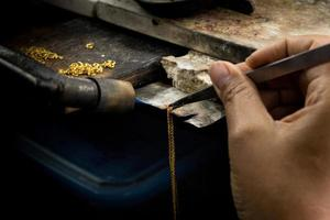 guldsmed som arbetar med ett oavslutat verk. foto