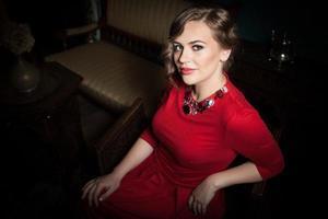 underbar dam i röd klänning som sitter i en vintage stol foto