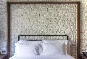 vita kuddar på ett klassiskt sovrum med vit tegelvägg foto