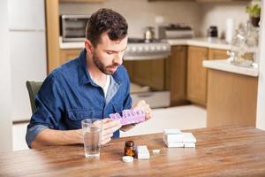 man organiserar sina piller hemma foto
