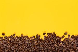 kaffebönor på gul bakgrund foto