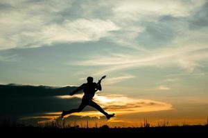 man spelar gitarr med solnedgång bakgrund foto
