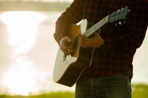 man spelar akustisk gitarr