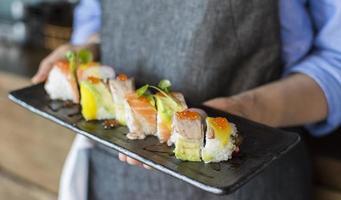 närbild av personen som håller sushi foto