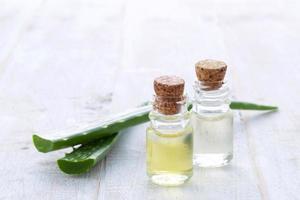 färsk aloe vera med aromolja på träbakgrund foto