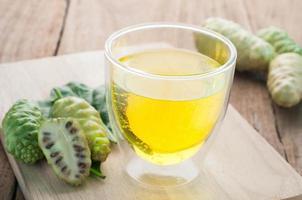 noni juice på glas och frukt på trägolv. foto