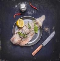 ingredienser förberedelse rå torsk örter citron stekpanna på nära håll foto