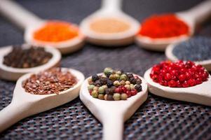 olika slags kryddor på träsked foto