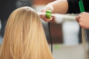 frisör som lockar hår med plattång foto