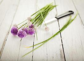 nyskördade blommande gräslök med kniv, rustik bakgrund foto