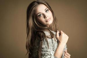 vacker brunett tjej. friskt långt hår. brun bakgrund