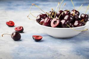 färska mogna svarta körsbär på en blå bakgrund foto