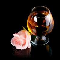 glas med alkohol och ros. foto