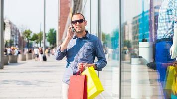 man shoppar med många färgade påsar i handen. foto