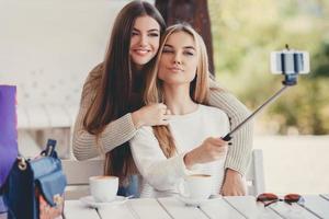selfie på ett café två trevliga flickvänner foto