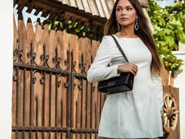 utomhus porträtt av vacker ung flicka i lyxig vit klänning.