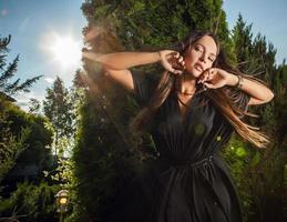 utomhus porträtt av vacker flicka i lyxig lång svart klänning.